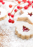 Christmas Cookies. Christmas Tree Linzer cookie with powdered icing sugar and red decorations in the background stock photo