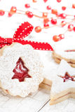 Christmas Cookies. Christmas Tree Linzer cookie with powdered icing sugar and red decorations in the background royalty free stock photos