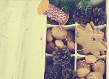 Christmas cookies, walnuts, nuts and pine cones in wooden box. Stock Photos