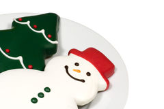 Christmas Cookies on White. Snowman and Christmas Tree cookies on a white plate. Perfect footer or corner piece for any Christmas design Stock Image