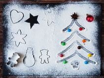 Christmas cooking. Xmas tree with decorations and candies made from flour on a dark table, ingredients for baking on dark stock photos