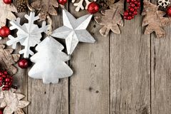 Christmas corner border with berries, rustic wood and metal ornaments on aged wood Royalty Free Stock Photo