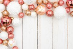 Christmas corner border of rose gold, white and gold ornaments on white wood stock images