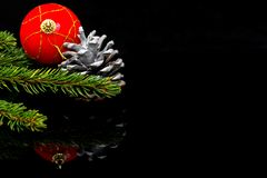 Christmas corner, focus on the painted spruce cone, decorations on black shiny surface stock photos