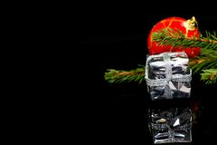 Christmas corner, focus on the tiny silver gift box on black shiny surface royalty free stock photography