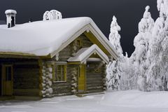 Christmas cottage. Wooden cottage in the forest covered by snow Royalty Free Stock Photography