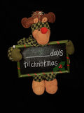 Christmas Countdown. A reindeer soft-toy holding a slate which counts the remaining days to Christmas, isolated on a black background Royalty Free Stock Image