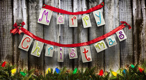 Christmas in the country. Merry Christmas sign made of tin and hung by red ribbon on a old weathered wooden fence.  Christmas lights are strung through pine Royalty Free Stock Photos