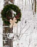 Christmas County Wreath. A Christmas wreath hanging from a tree in a snowy forest Stock Photo