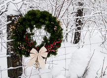 Christmas County Wreath Horizontal. Christmas wreath hanging on a fence post against a snowy background Royalty Free Stock Photo
