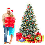 Christmas couple. Young happy couple near  a Christmas tree. Isolated over white background Royalty Free Stock Photo