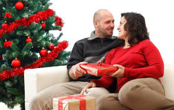 Christmas couple. Young man giving a gift to his girlfriend near the Christmas tree Royalty Free Stock Photography