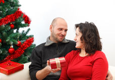 Christmas couple. Young man giving a gift to his girlfriend near the Christmas tree Royalty Free Stock Images