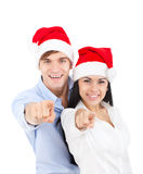 Christmas couple. Christmas holiday couple point finger at you looking at camera in red new year hat cap, isolated over white background Stock Photography