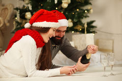 Christmas couple celebrating by opening bottle of champagne Stock Photo