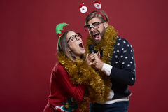 Christmas couple. Great fun while having karaoke performance Royalty Free Stock Photos