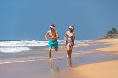 Christmas couple happy relaxing on beach running on sand.  Royalty Free Stock Photos