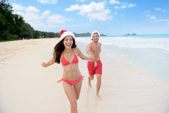 Christmas couple happy relaxing on beach travel. Christmas couple happy relaxing on white sand beach running on sand in bikini and swimsuit. Asian women and men Stock Photos