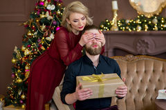 Christmas couple, happy young female surprise man cover his eyes Stock Photography