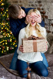 Christmas couple, happy young female surprised by man cover her Stock Images