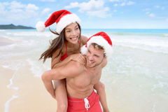Christmas couple having fun on beach vacation. Doing piggyback. Laughing funny young friends playing on beach during winter holidays wearing santa hats Royalty Free Stock Image