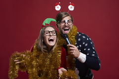Christmas couple. Having karaoke party during christmas time Royalty Free Stock Images