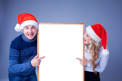 Christmas couple holding white board with empty Royalty Free Stock Photo