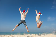 Christmas couple jumping. Christmas couple having fun on a beach Royalty Free Stock Image