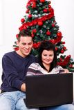 Christmas couple with laptop. A shot of smiling couple using laptop to shop online in front of the Christmas tree Stock Image