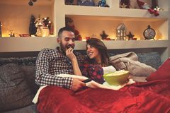 Christmas couple looking movie and eat popcorn in bed. Young Chrismas couple enjoy together looking movie and eat popcorn in bed royalty free stock photography
