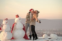 Christmas couple in love of man and girl with snowman. Christmas couple in love of men and girl santa claus with snowman outdoor, winter holiday and party stock photos