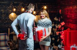 Christmas couple in love. Mutual new-year-gifts. Beloved is hiding a present behind back. The girl is holding a large. Red box in her hands stock image