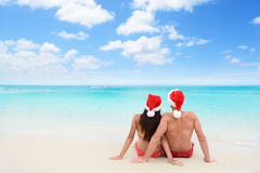 Christmas couple in love on travel beach holidays. Christmas couple in love lying down relaxing on white sand beach sun tanning in tropical travel destination Stock Photos
