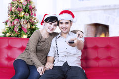 Christmas couple with santa's hats and holding remote control Stock Photography