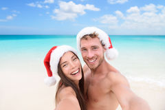 Christmas couple selfie picture on beach vacation. Happy young adults smiling at camera taking self-portrait wearing santa hats. Multiracial Caucasian and Stock Photos