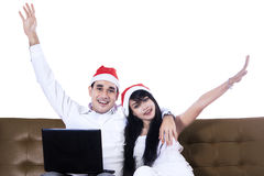 Christmas couple shopping online. Christmas couple buying christmas gift online sitting on brown sofa Stock Images