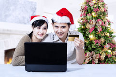 Christmas couple shopping online at home. Young couple in Christmas online shopping at home Stock Photography