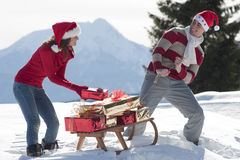 Christmas couple with sled. And gifts Royalty Free Stock Photos
