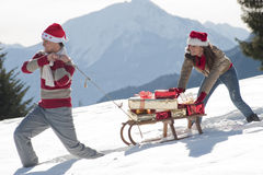 Christmas couple with sled and gifts Royalty Free Stock Images