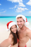 Christmas couple taking selfie on beach holidays. Happy couple on Christmas travel holidays taking selfie picture with smartphone wearing santa hat during their Stock Photo