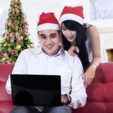 Christmas couple using a laptop Royalty Free Stock Photos