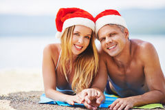 Christmas couple. Young couple in Santa hats and swim-wear relaxing on beach Royalty Free Stock Images