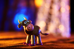 Christmas cow from plasticine. On the background of lights Stock Photography