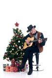Christmas cowboy. Christmas tree with presents and cowboy playing on his guitar, white background Royalty Free Stock Photo