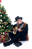 Christmas cowboy. Christmastree with presents and cowboy playing on his guitar, white background Stock Images
