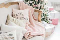 Christmas coziness christmas tree, pillows on a couch feather pink veil blanket of thick yarn, Christmas cosiness.  Royalty Free Stock Image