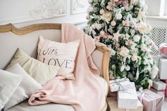 Christmas coziness christmas tree, pillows on a couch feather pink veil blanket of thick yarn, Christmas cosiness.  Stock Photo