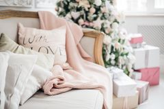 Christmas coziness christmas tree, pillows on a couch feather pink veil blanket of thick yarn, Christmas cosiness.  Royalty Free Stock Images