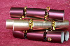 Christmas crackers. Golden and red Christmas crackers on purple background Royalty Free Stock Photos