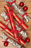 Christmas Crackers. Homemade Christmas crackers on wooden background with red baubles Royalty Free Stock Photos